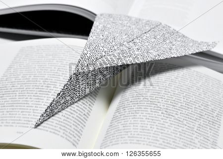 closeup of a paper plane, made with a printed paper with non-sense words, on an open book