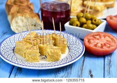 closeup of a plate with tortilla de patatas, spanish omelet, served as tapas, a glass with tinto de verano, bread and a bowl with olives on a colorful blue wooden table