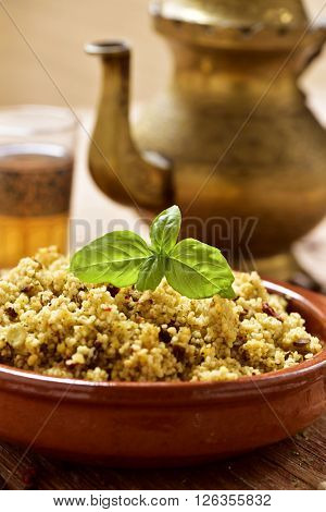 closeup of an earthenware bowl with couscous with vegetables, some ornamented glasses with tea and a golden teapot on a rustic wooden table