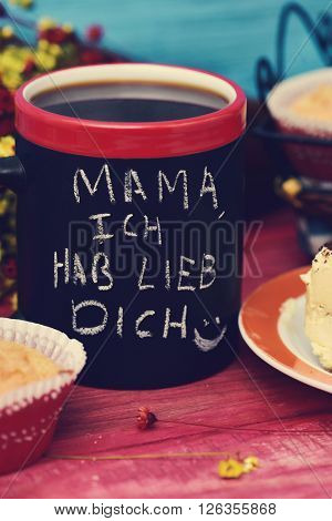 the sentence mama ich hab lieb dich, I love you mom in german handwritten with chalk in a black mug with coffee, with some muffins in the background in a set table for breakfast
