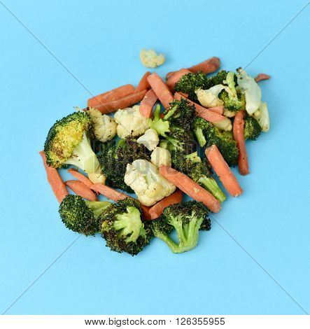 high-angle shot of some different sauteed vegetables, such as cauliflower, broccoli and carrot, on a blue background