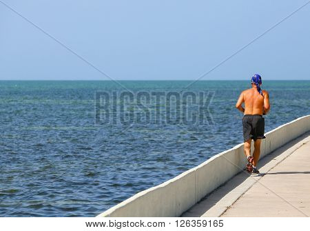 KEY WEST, USA - MAY 10, 2015: Man running along the blue sea in blazing sun on the Florida Keys Overseas Heritage Trail. He is wearing only running shorts and a bandana.