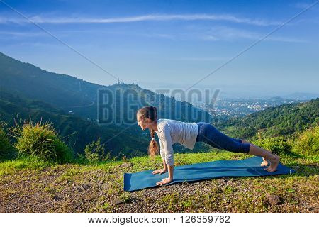Woman doing Hatha yoga asana Kumbhakasana plank pose  outdoors in mountains
