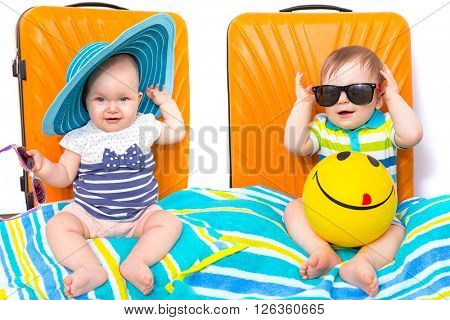 Baby girl and boy twins packed for travel with orange luggage bags
