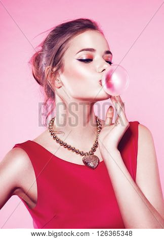 Beautiful young woman blowing bubble gum pink background in studio