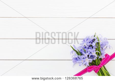Bouquet Of Spring Flowers Decorated With Pink Ribbon On White Wooden Background. Top View, Copy Spac