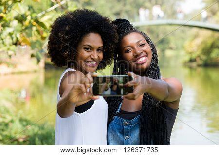 Afro friends having fun in the park taking selfie