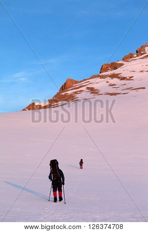 Two Hikers In Sunrise Snowy Plateau