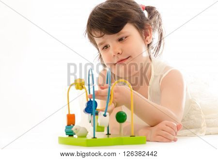 Sweet toddler girl concentrated playing with educational baby toy isolated on white background