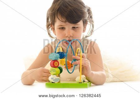 Sweet toddler girl concentrated playing with educational baby wooden toy isolated on white background