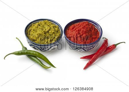 Bowls with green and red Moroccan harissa on white background