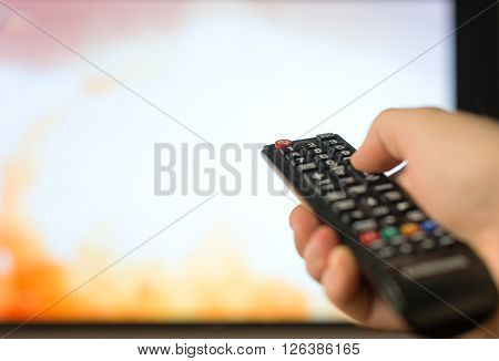 Male hand holding TV remote control over TV background