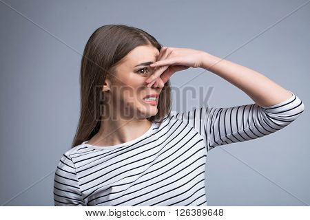 Horrible smell. Pleasant beautiful nice girl closing her nose and looking aside while standing isolated on grey background