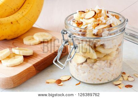 Banana nut overnight oats with in snap lid glass jar on white marble