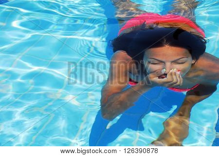teenage girl diving in the blue transparent swimming pool underwater holding breath
