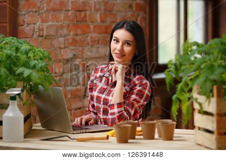 Effortless. Charming female wearing glasses sitting in front of a laptop in a greenhouse.