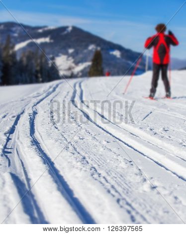 Cross-country skiing in Alps. Man cross-country skiing on a lovely sunny winter day. Focus on the ski run