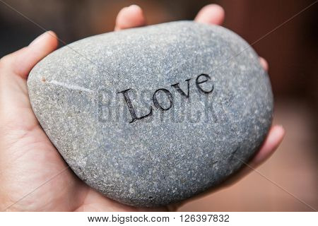 Hands holding pebble stones with the word love