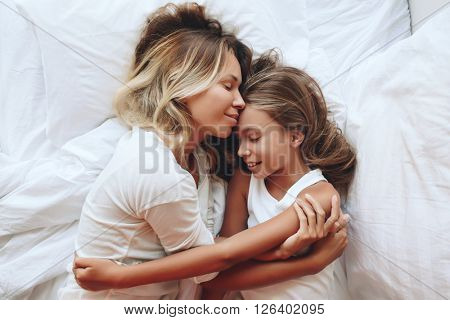 Mom with her tween daughter relaxing in bed, positive feelings, good relations. Top view. poster