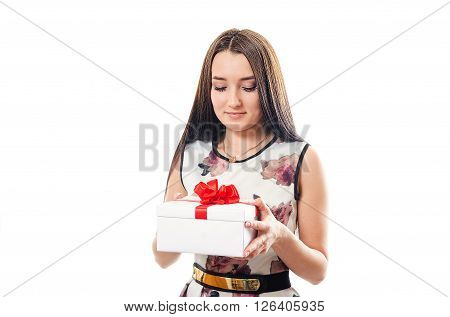 The beautiful girl in a dress looks at a gift in a white box with a red bow