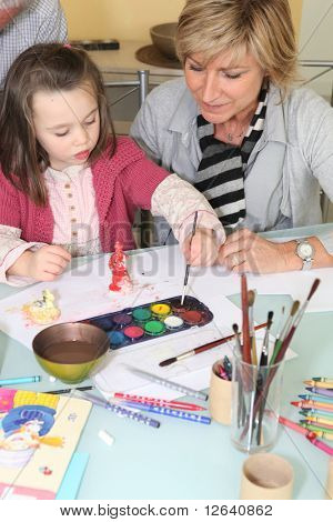 Senior woman making watercolors with a girl