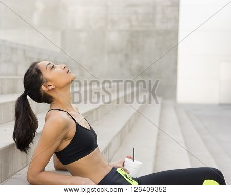 Woman recovering from workout wearing athletic clothing -  sitting down head looking up at copy space text area