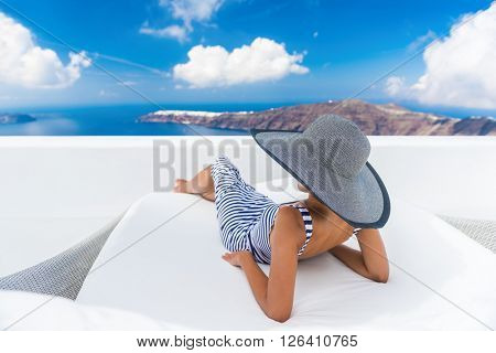Vacation travel woman relaxing enjoying Santorini looking at famous view of Caldera. Young lady lying down on sun bed sofa lounge chair on holidays. Amazing view of sea. Europe travel destination.