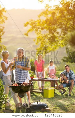 smiling grandparents drinking wine and enjoying picnic with family