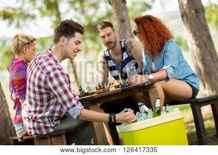 Guy on picnic in forest takes out cold beer from handheld refrigerator