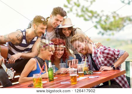 Youngsters on picnic in wood watching photos on mobile phone