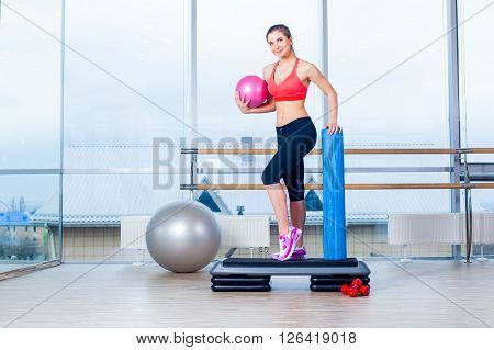 Fitness girl, wearing in sneakers, red top and black  breeches, posing on step board with ball, on the sport equipment background, in the gym.