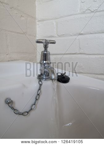 Unhygienic grimy wash hand basin tap with running water