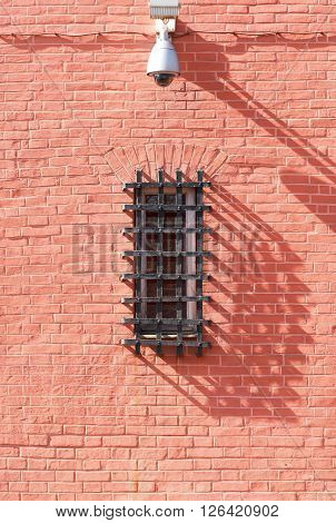 Barred window and security camera on a brick wall