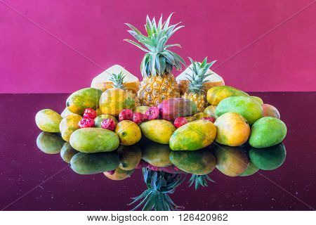 A selection of well-known famous market fresh tropical Mauritius fruit on a purple glass table in the magenta background. The selection includes Coconut Rose Apple Mango and Pineapples.