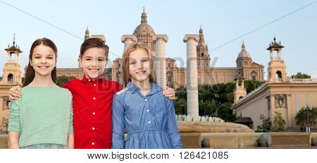 childhood, travel, tourism, friendship and people concept - happy smiling boy and girls hugging over national museum of barcelona background