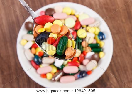Pills on teaspoon and capsules or supplements for therapy in background on plate concept of treatment