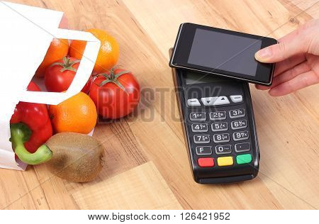 Using credit card reader payment terminal with mobile phone with NFC technology and fresh fruits and vegetables in paper shopping bag cashless paying for shopping