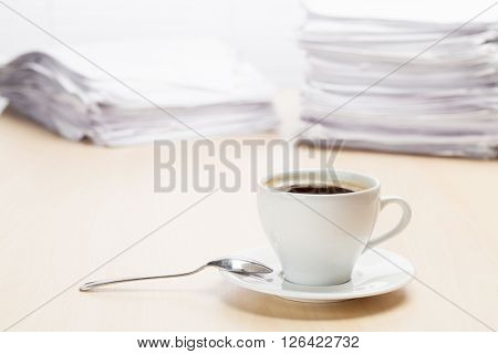 Office workplace with coffee cup and lot of documents on wood desk table in front of window with blinds