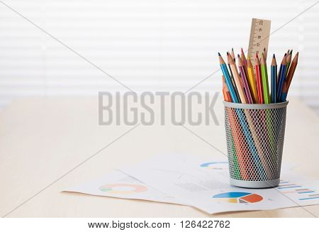 Office desk with charts and supplies on wood desk table in front of window with blinds. View with copy space