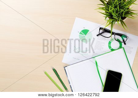 Office desk workplace with charts, phone, plant and notepad on wooden table. Top view with copy space