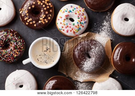 Colorful donuts and coffee on stone table. Top view