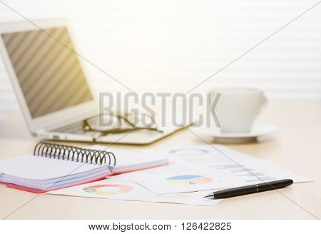 Office workplace with coffee cup, laptop and supplies on wood desk table in front of window with blinds