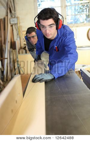 Carpenter and apprentice working in studio
