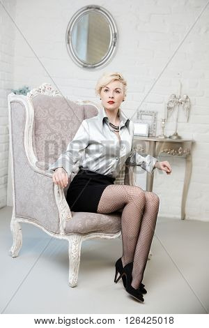 Sexy blonde woman sitting in armchair in baroque interior.