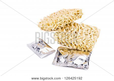 Uncooked Instant Noodles With Flavoring Packets On White Background