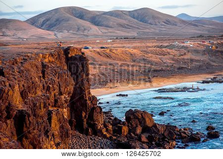 EL COTILLO, FUERTEVENTURA ISLAND, SPAIN - SIRCA JANUARY 2016: View on El Cotillo coastline with huge cliff and mountains on the background on Fuerteventura island. This beach is popular among surers