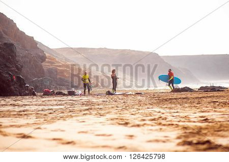 EL COTILLO, FUERTEVENTURA ISLAND, SPAIN - SIRCA JANUARY 2016: Surfers on El Cotillo sandy beach. El Cotillo beach is very popular for surfing on Fuerteventura island