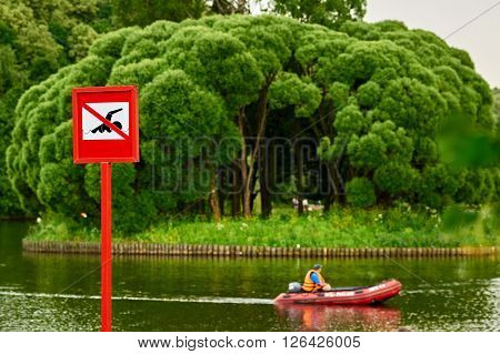 A no swimming danger sign at the beach. there is distance boat