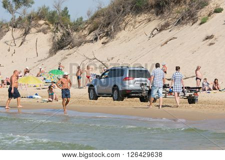 Anapa Russia - September 20 2015: Jeep with insolent driver rides on the beach with holidaymakers