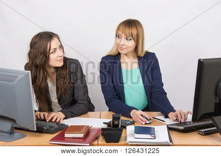 Office Worker With Superior Looks At Grim Colleague Sitting Next